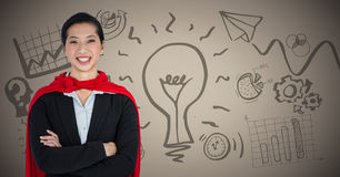 Business woman superhero with arms folded against brown background with idea doodles Stock Images