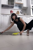 Business woman sweeps. Business woman in the kitchen of his house sweeps Stock Photography