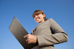 Business woman with tablet. Business woman on the tablet and smiles at the blue sky Royalty Free Stock Photography