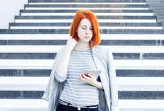 Business woman with a tablet in hands looking down on the background of the stairs Royalty Free Stock Image