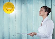 Business woman with tablet looking up at emoji and flare against blue wood panel. Digital composite of Business woman with tablet looking up at emoji and flare Royalty Free Stock Photography
