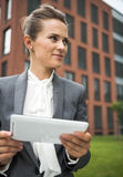 Business woman with tablet PC near office building looking aside Royalty Free Stock Photo