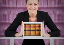 Business woman with tablet showing book spines against blurry bookshelf with pink overlay Royalty Free Stock Photos