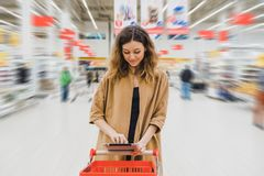 Business woman with tablet is standing with cart in the supermarket, girl is choosing food and looking at the shopping. List Stock Photos