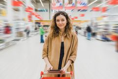 Business woman with tablet is standing with cart in the supermarket and looking straight.  Stock Photography