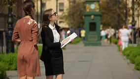 Business woman with tablet talking with other woman on the street of the city. stock footage