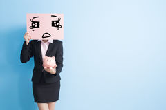 Business woman take billboard. Businesswoman take cry billboard and show piggy bank to you isolated with blue background Royalty Free Stock Images