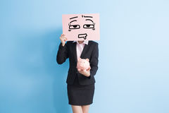 Business woman take billboard. Businesswoman take tired billboard and show piggy bank to you  with blue background Stock Photos