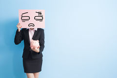 Business woman take billboard. Businesswoman take tired billboard and show piggy bank to you isolated with blue background Royalty Free Stock Image