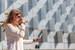 Business woman takes a coffee and checks her mobile phone while walking in front of a large office building stock images