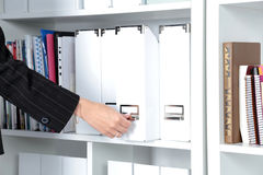 Business woman takes a folder that is on the shelf in the office. Royalty Free Stock Photos