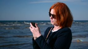 Business woman takes out her cellphone mobile phone and dials a number. Business woman uses her mobile phone by the sea stock video