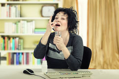 Business woman takes a pill sitting at the desk Royalty Free Stock Photos