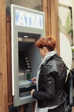 Business woman taking money from ATM Stock Image