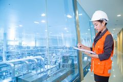 Business woman taking notes in production area of factory stock image