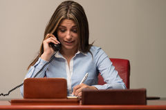 Business Woman Taking Notes And Talking On Phone. Beautiful Young Woman Working Taking Notes And Talking On Phone- Businesswoman Working Online Royalty Free Stock Images