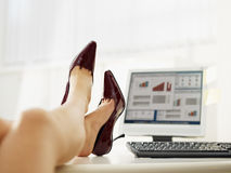 Business woman taking off shoes Royalty Free Stock Image