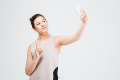 Business woman taking selfie with smartphone and showing peace gesture Stock Images