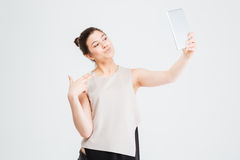 Business woman taking selfie with tablet and making duck face Stock Images