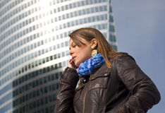 Business woman talking on a cell phone. Beautiful business woman talking on a cell phone against a glass skyscraper Royalty Free Stock Photo