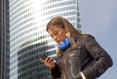 Business woman talking on a cell phone. Beautiful business woman talking on a cell phone against a glass skyscraper Royalty Free Stock Images