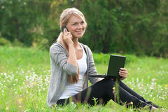 Business woman talking on a cell phone. Young  business woman using laptop and talking on a cell phone outdoors Royalty Free Stock Photography