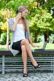 Business woman talking on a cell phone. Young attractive business woman talking on a cell phone and using laptop outdoors Stock Photo