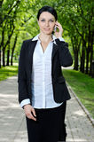 Business woman talking cell phone,. Beautiful business woman talking cell phone and walking in the park Stock Images