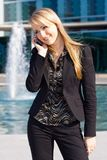 Business woman talking on a cell phone. Happy young blond business woman talking on a cell phone Royalty Free Stock Images