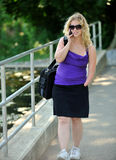 Business woman talking on cell phone - disability. Portrait of attractive blonde business woman who is missing part of left arm (congenital amputation) walking royalty free stock image