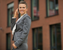 Business woman talking cell phone. In front of office building Royalty Free Stock Image
