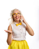 Business woman talking on cell phone. The girl is dressed in a blouse, a bow tie and glasses. Conversation Royalty Free Stock Image