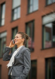 Business woman talking cell phone. Happy business woman talking cell phone in front of office building Royalty Free Stock Images