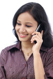 Business woman talking on cell phone. Happy young business woman talking on cell phone against white background Royalty Free Stock Images