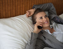 Business woman talking cell phone in hotel room. Business woman talking cell phone on bed in hotel room Stock Image