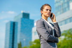 Business woman talking cell phone. Portrait of happy business woman talking cell phone in office district Stock Image