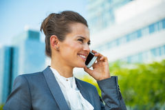 Business woman talking cell phone. Smiling business woman talking cell phone in front of office building Royalty Free Stock Photos