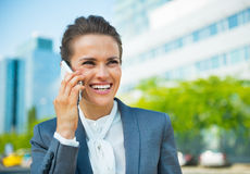 Business woman talking cell phone. Smiling business woman talking cell phone in office district Stock Photos