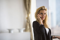 Business woman talking on cell phone while standing on the balcony of the office. Stock Photo