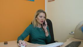 Business woman talking on cellphone and using computer in office. Beautiful blonde businesswoman talking on cellphone and using computer at workplace in office stock footage
