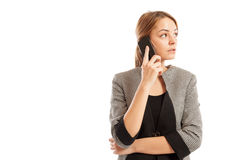 Business woman talking on her smartphone and thinking Stock Images