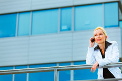 Business woman talking mobile near office building Stock Photo