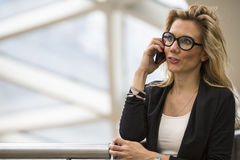 Business woman talking on mobile phone in business center. Royalty Free Stock Photography
