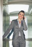 Business woman talking mobile phone in elevator Royalty Free Stock Photo