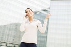 Business woman talking on mobile phone in front of office Stock Images