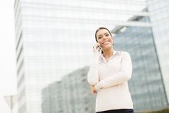 Business woman talking on mobile phone in front of office Royalty Free Stock Photo