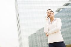 Business woman talking on mobile phone in front of office Royalty Free Stock Image