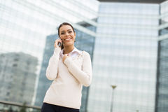 Business woman talking on mobile phone in front of office Royalty Free Stock Photography