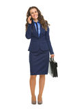 Business woman talking mobile phone. Full length portrait of happy business woman talking mobile phone Stock Image