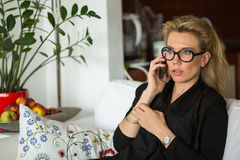 Business woman talking on mobile phone sitting on the couch. Stock Photography